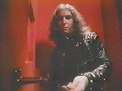Jim Steinman : still taken from Dance In My Pants music video. Jim handles coins to insert into a coin-operated device
