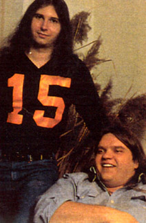 Jim Steinman (left) in a sports jersey, Meat Loaf (right) seated