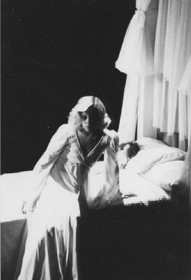 Ellen Foley as Wendy, dressed in all white and looking contemplative as she sits on the edge of her bed.